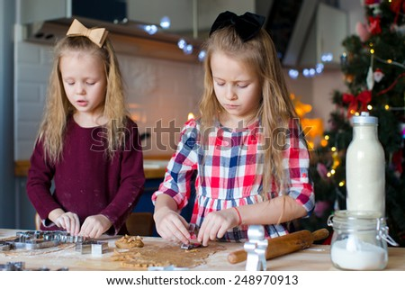 Little girls baking gingerbread cookies for Christmas at home kitchen - stock photo