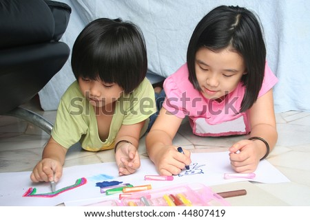 Little girls doing art painting at home together - stock photo