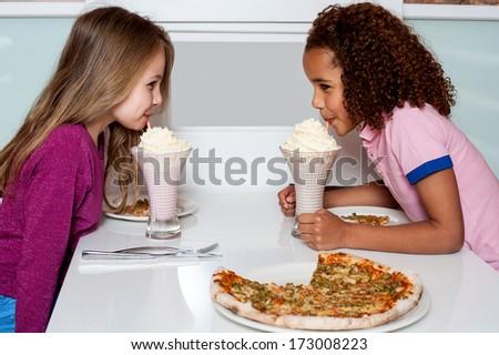 Little girls drinking strawberry shake in a restaurant - stock photo