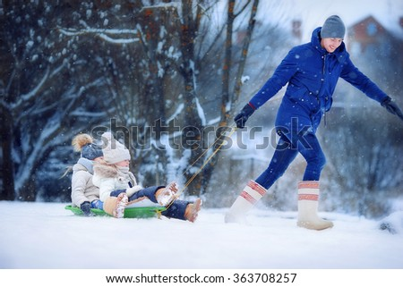 Little girls enjoying sledding. Father sledding his little adorable daughters. Family vacation on Christmas eve outdoors - stock photo