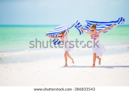 Little girls having fun running with towels on tropical beach  - stock photo