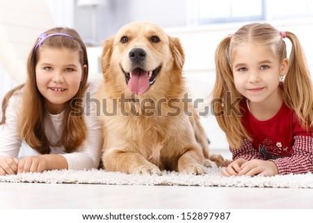 Little girls lying prone on floor, golden retriever between them. - stock photo