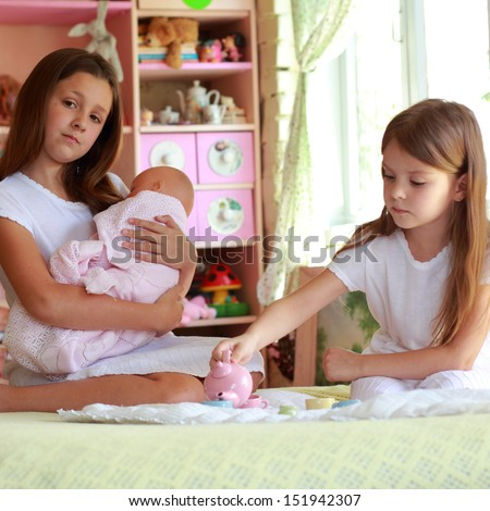 Little girls playing with her baby doll and pretending mom - stock photo