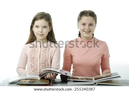 Little girls read books at the table isolated on white - stock photo