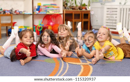 Little girls show sign OK. Kindergarten children - stock photo