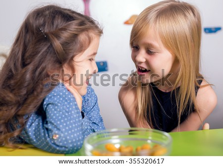 Little girls sitting and talking in the playroom - stock photo