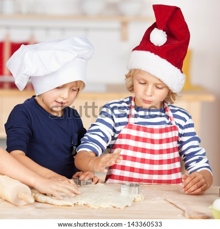 Little girls standing at a kitchen counter baking Christmas cookies cutting pastry with a cookie cutter - stock photo