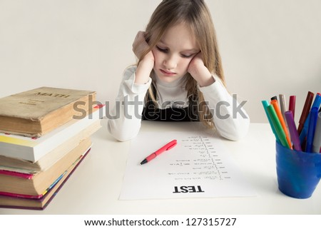 Little girls studying, thinking hard on a math test - stock photo