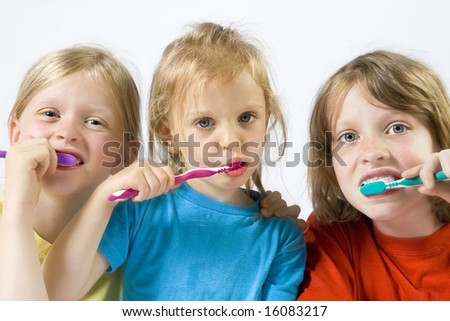 Little girls wearing colorful t-shirts brushing teeth - stock photo