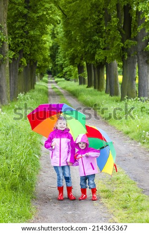 little girls wearing rubber boots with umbrellas in spring alley - stock photo