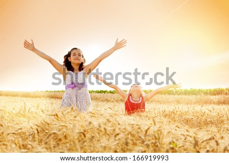 Little girls with arms outstretched in a wheat field,flare light - stock photo