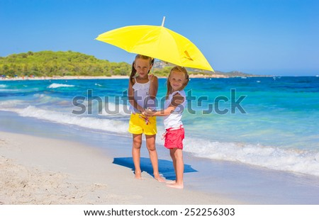 Little girls with big yellow umbrella during tropical beach vacation - stock photo