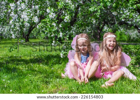 Little girls with butterfly wings in the blossoming apple orchard - stock photo
