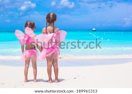 Little girls with butterfly wings on beach summer vacation - stock photo