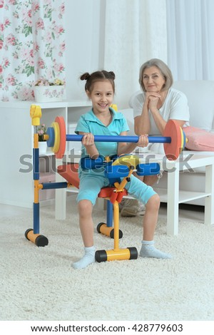 little granddaughter doing exercise - stock photo