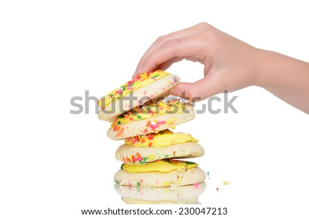 little hand picking up sugar cookie with frosting isolated white background - stock photo