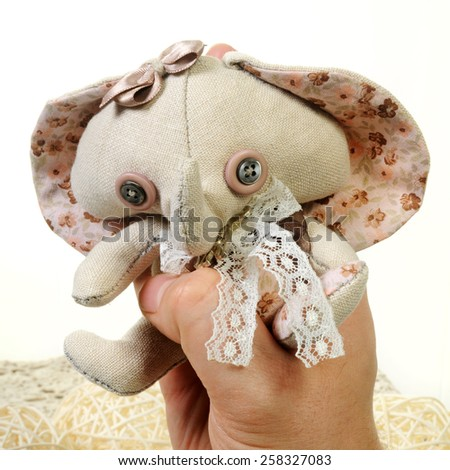 little handcrafted vintage style soft toy elephant in a man's hand isolated on White background - stock photo