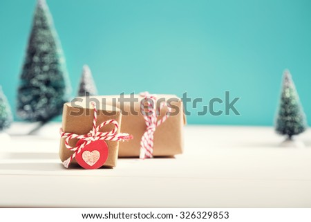 Little handmade gift boxes in a snow covered miniature evergreen forest - stock photo