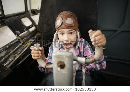 little happy boy dreaming of being pilot - stock photo