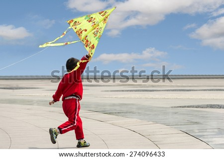 Little happy boy playing with flying kite - stock photo