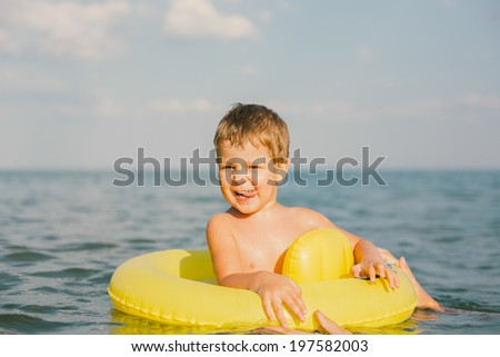 Little happy boy swimming and playing at sea with rubber ring - stock photo
