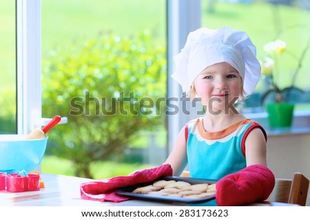 Little happy child, adorable toddler girl wearing white chef hat and red gloves helping mother cooking delicious pastry in the kitchen - stock photo