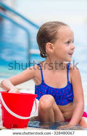 Little happy cute girl with beach toys in outdoor swimming pool - stock photo