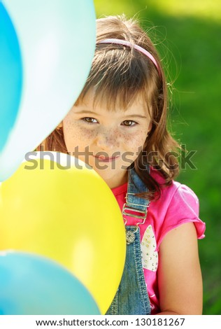 Little happy gir holding colorful balloons - stock photo
