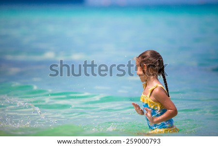 Little happy girl at swimsuit having fun in clear sea - stock photo