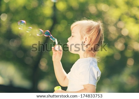 Little happy girl blowing soap bubbles in the park - stock photo