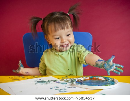 Little happy girl discovering finger painting - stock photo