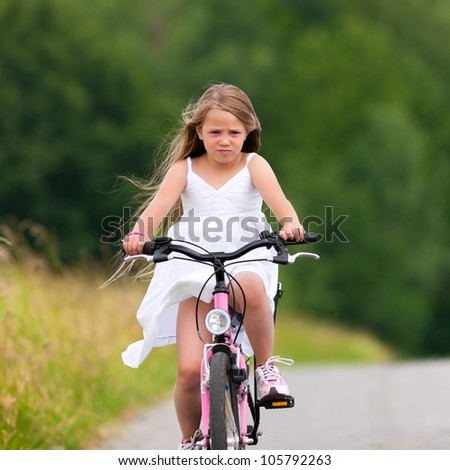 Little happy girl has a weekend excursion on her bike on a summer day in beautiful landscape - stock photo