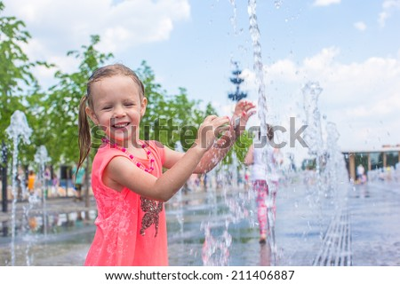 Little happy girl have fun in street fountain at hot sunny day - stock photo