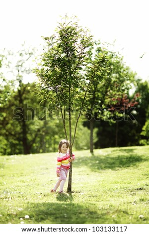 little happy girl near the tree - stock photo