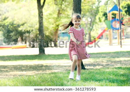 Little happy girl playing in park near the playground - stock photo