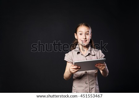 Little happy girl surprised, with positive emotional facial expression stands with white Digital Table. Female child studio portrait wih modern device at black background with copy space - stock photo