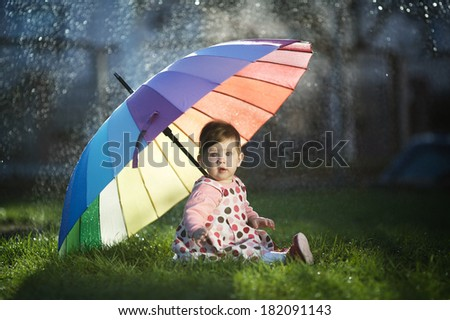 little happy girl with a rainbow umbrella in park - stock photo