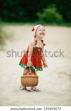 little happy girl with basket full of strawberries - stock photo