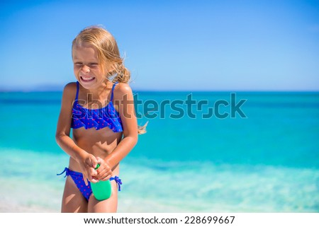 Little happy girl with suntan lotion bottle during beach vacation - stock photo