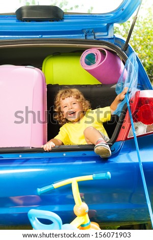 Little happy laughing three years old boy sitting in the car trunk with bags, net-scoop and mate for the trip in the car - stock photo