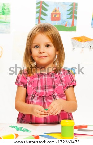 Little happy little young girl gluing on creative art class - stock photo