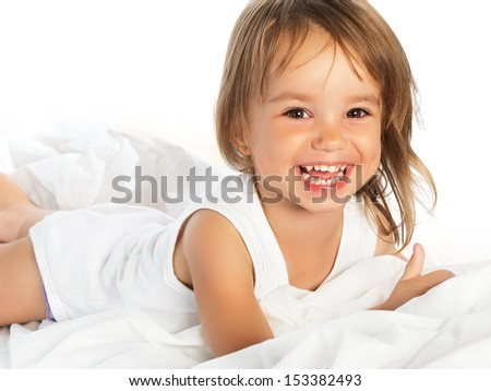 little happy smiling cheerful girl in a white bed isolated - stock photo