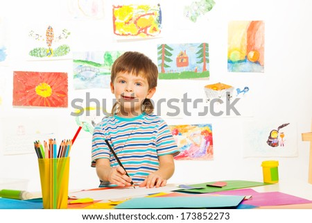 Little happy smiling 3 years old boy with glue stick and pencils in the art developmental class - stock photo