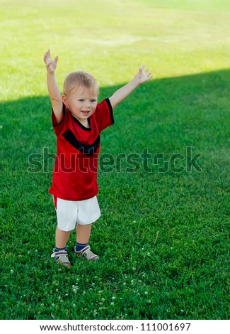 Little happy soccer player rejoices after score goal - stock photo