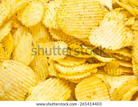 little heap of golden corrugated potato chips - stock photo