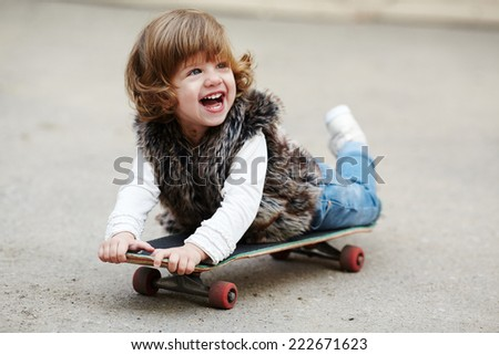 little hipster girl with skateboard portrait - stock photo