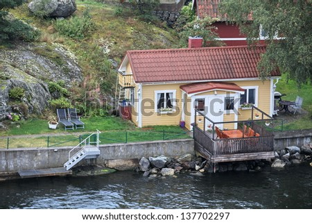 little house on the beach with jetty - stock photo