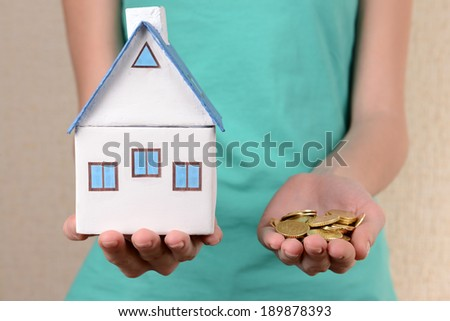 Little house-toy and coins in woman hands close-up - stock photo