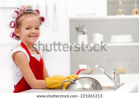 Little housekeeping girl - washing the dishes with a happy smile - stock photo