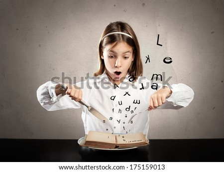 little hungry girl sitting at table holding forks in front of a book - stock photo